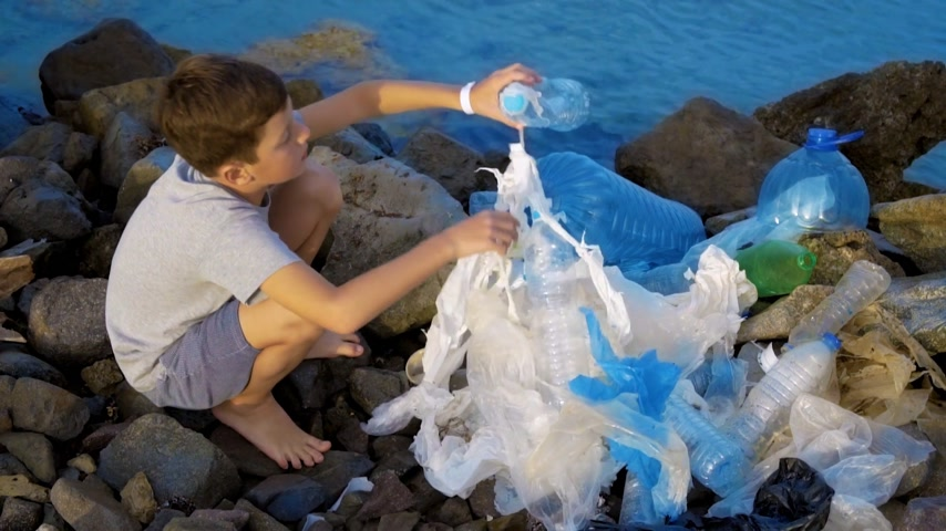 приморский : Litle child volunteer cleaning up the beach at the sea. Safe ecology concept.