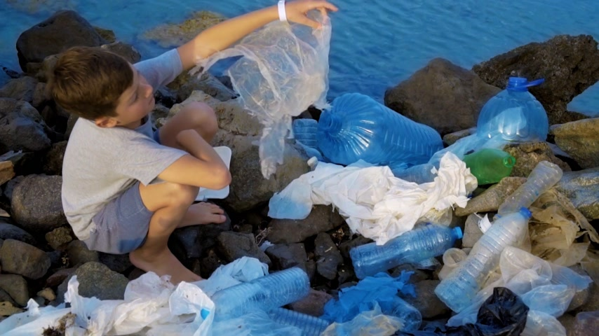 dobrovolník : Litle child volunteer cleaning up the beach at the sea. Safe ecology concept.