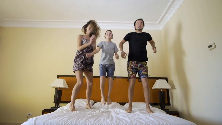 ágynemű : Happy family with little son jumping on bed at home