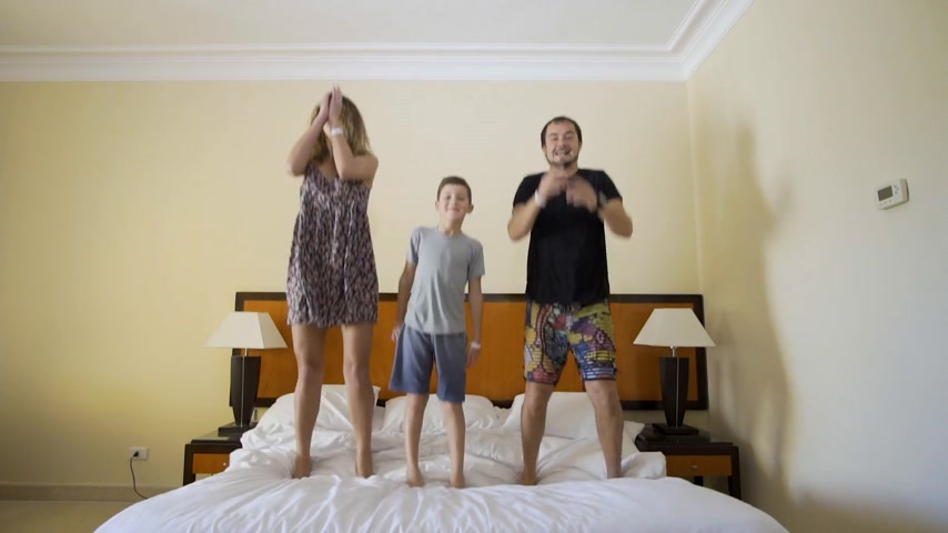 ágynemű : Happy family jumping on the bed. Happy family concept. Father, mother and little boy jump on the bed