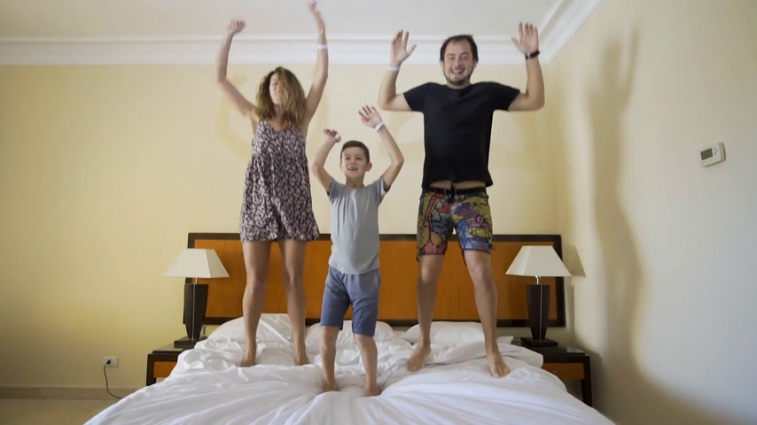 szórakoztatás : Happy family jumping on the bed. Happy family concept. Father, mother and little boy jump on the bed