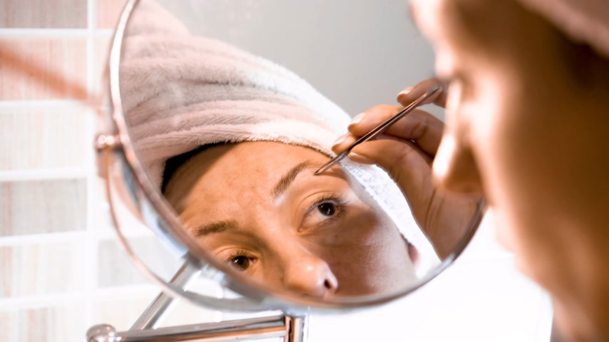 tweezing : Adult woman corrects eyebrows and looking in the mirror