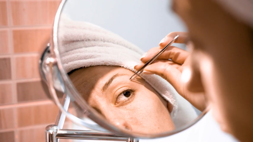 кавказский : Adult woman corrects eyebrows and looking in the mirror