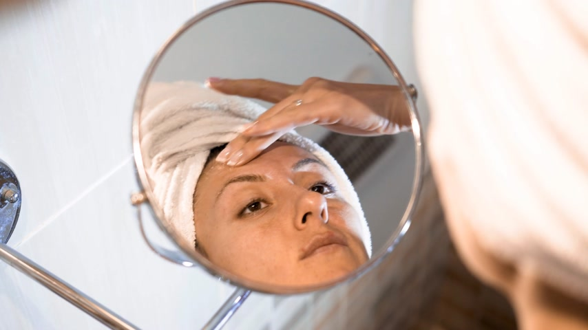 mimos : The woman applying face cream on skin. Caucasian female in front of make-up mirror
