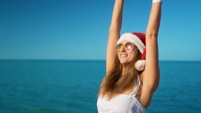 świety mikołaj : The happy girl in santa claus hat rejoices at sea