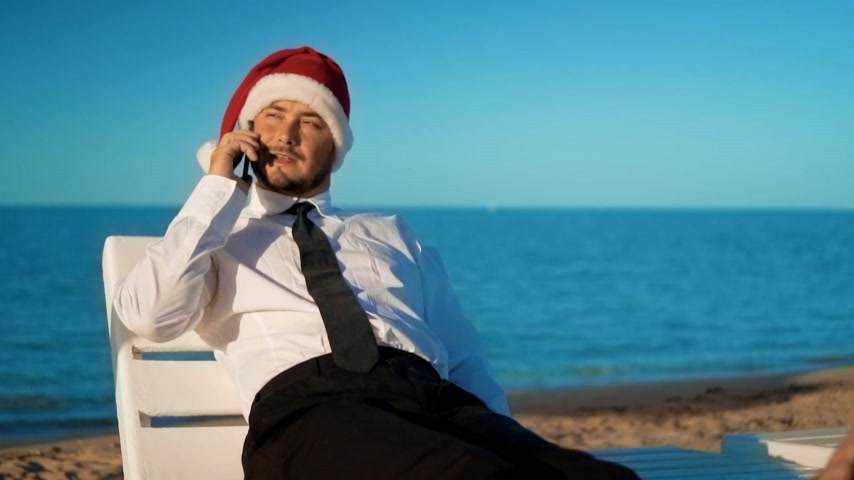 świety mikołaj : businessman in santa claus hat sitting on a lounger on the background of the sea