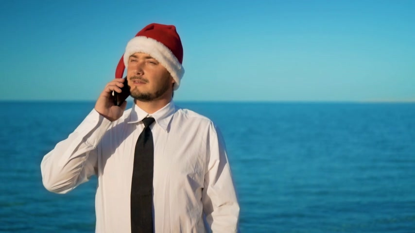 świety mikołaj : The businessman on the background of the beautiful sea talking on the phone, solving in cases in santa claus hat