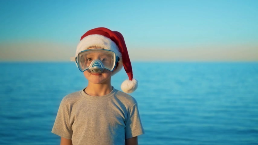 świety mikołaj : The boy in the Christmas hat stands against the sea in diving mask and snorkel