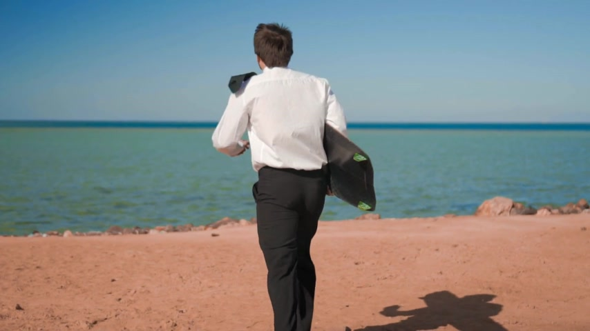 kierownik : The businessman in suit runs to the sea with a kitesurf board Wideo