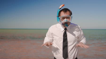 kravata : he businessman on the background of a beautiful sea in a mask and snorkel imitates swimming