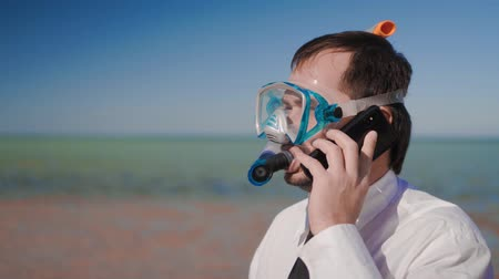 šnorchl : The businessman on the beach talking on the phone in a snorkelling mask and snorkel