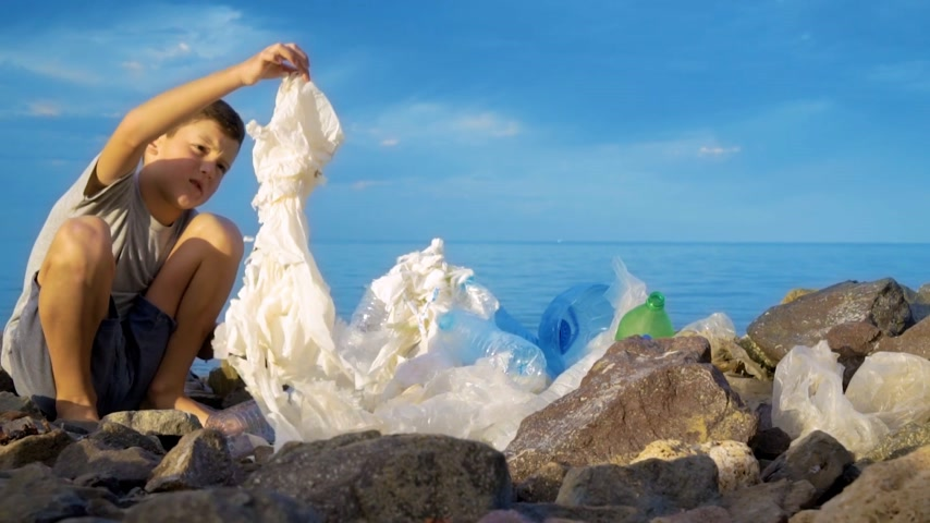 skládka : Litle child volunteer cleaning up the beach at the sea. Safe ecology concept.