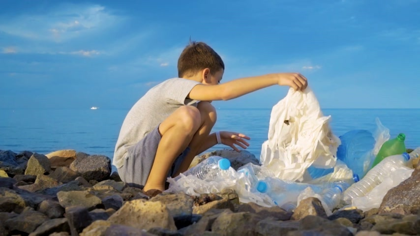 reciclagem : Litle child volunteer cleaning up the beach at the ocean. Safe ecology concept.
