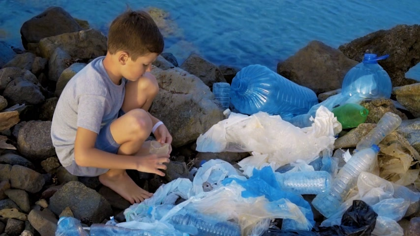 plastics : Litle child volunteer cleaning up the beach at the ocean. Safe ecology concept.