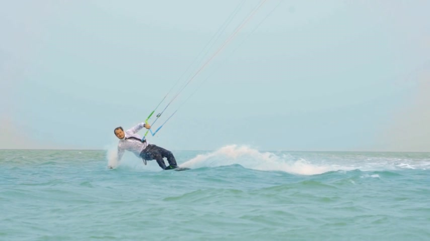 deli : businessman rides a kite in the tropical ocean and performs tricks Slow motion