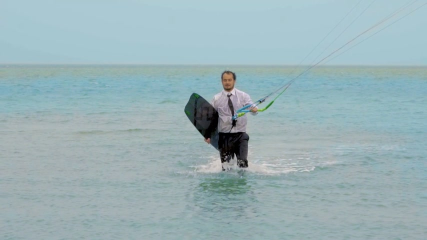 uçurtma : businessman rides a kite in the tropical ocean and performs tricks Slow motion