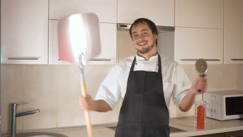 cozinhar : Attractive young funny man dancing while cooking in the kitchen at home