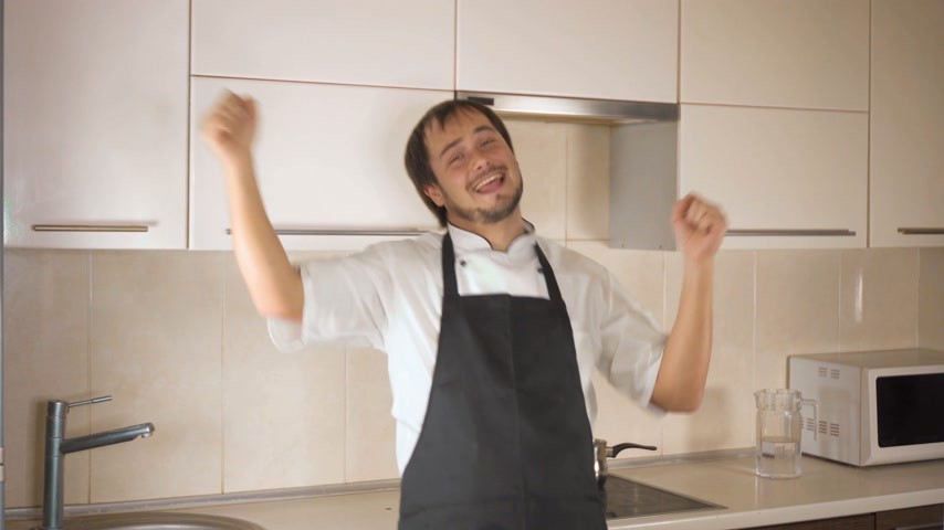 garnishing : Attractive young funny man dancing while cooking in the kitchen at home