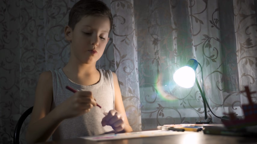pré escolar : Little boy sitting at table and drawing with colored pencils in the light of a lamp