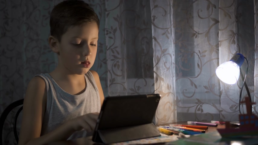 estudo : Child Uses Tablet For Studying, Boy Writing Homework in Night Internet Usage 4K