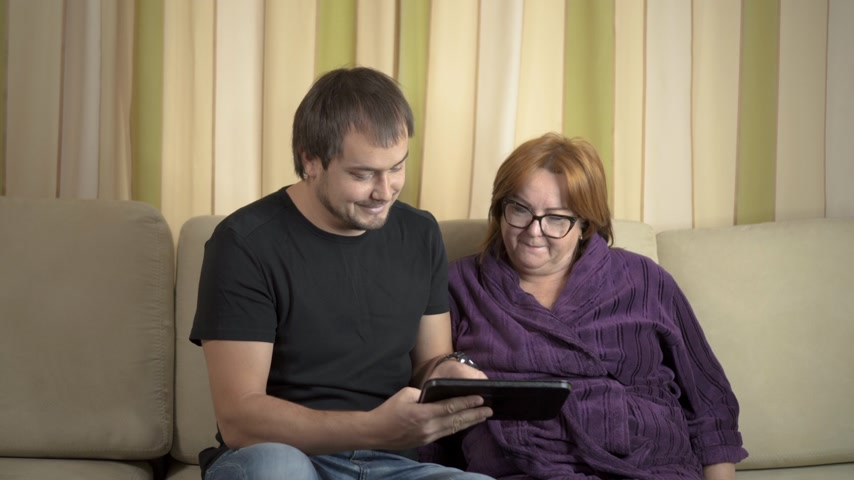 buying online : Young man Helping Her Grandmother For Using A Digital Tablet and credit card Stock Footage
