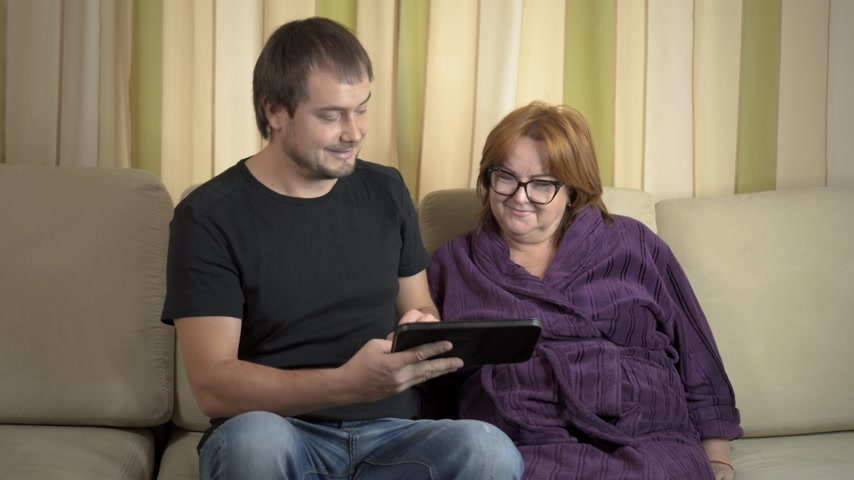 gadżety : Young man Helping Her Grandmother For Using A Digital Tablet and credit card Wideo