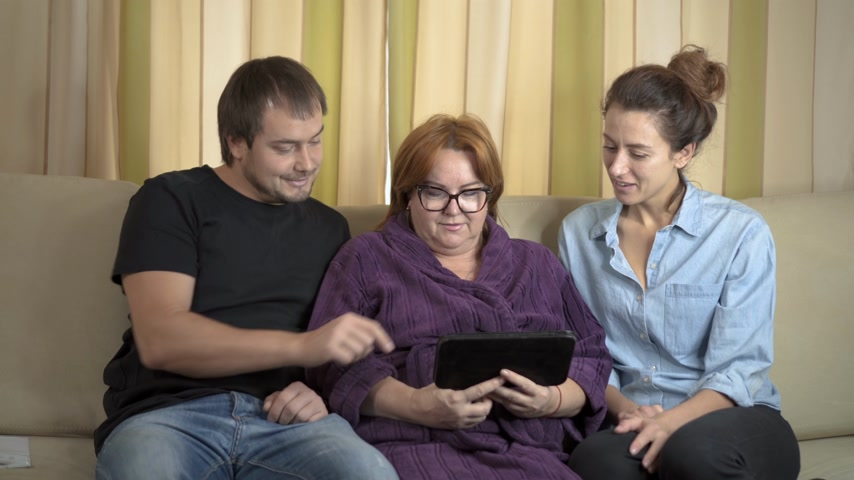 touchpad : Caring young home support workers showing elderly gentlewoman how to use a computer tablet.
