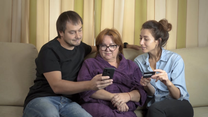 дебет : Senior mother and her young daughter and son using tablet at home. Shopping with credit card on cellphone. Teen granddaughter teaching grandmother how to use mobile and make purchases online