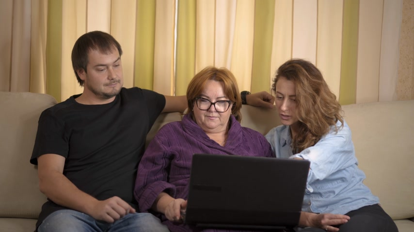 razem : Cheerful young home support workers showing elderly gentlewoman how to use a computer.