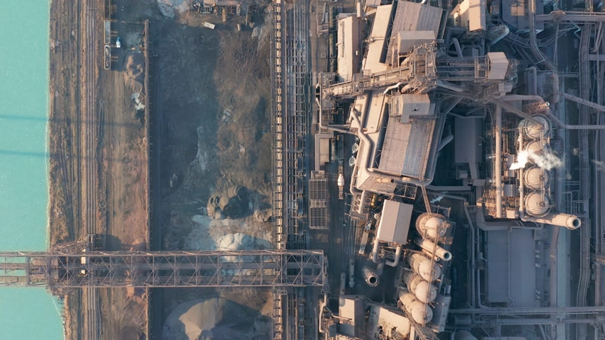 poluir : Aerial view over industrialized city with air atmosphere and river water pollution from metallurgical plant near sea. Dirty smoke and smog from pipes of steel factory and blast furnaces. Ecological