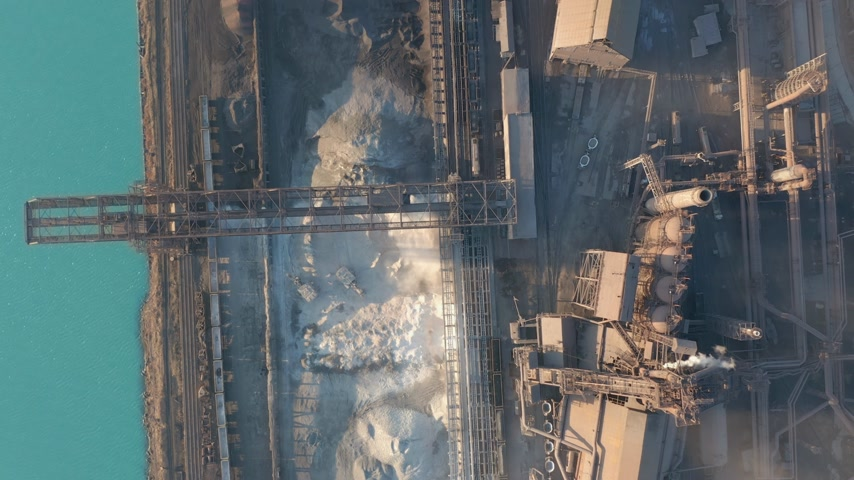 metallurgical : Aerial view over industrialized city with air atmosphere and river water pollution from metallurgical plant near sea. Dirty smoke and smog from pipes of steel factory and blast furnaces. Ecological