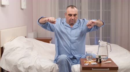 ülő : sick elderly man sits on a bed and chooses drugs and pills.