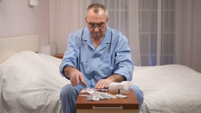 nachtkleding : Old man sitting in pajama on bed with pills in bowl on night table, depressed