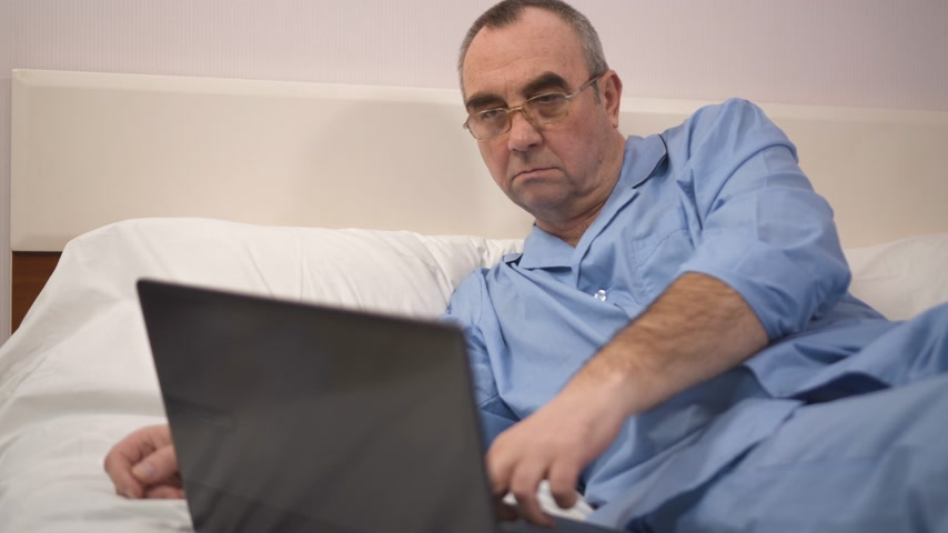 relaks : Senior man using laptop on bed in bedroom at home 4k
