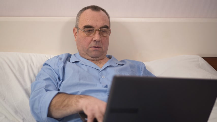 relax : Senior man using laptop on bed in bedroom at home 4k