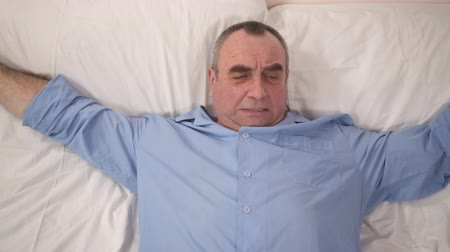 хорошее здоровье : Handsome senior man waking up in good mood at home after nice calm night. Happy male pensioner smiling lying in bed, sleeping on comfortable mattress and pillow, peaceful rest. Retirement relaxation Стоковые видеозаписи