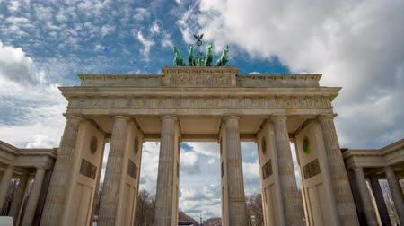 embléma : Time lapse. Brandenburg Gate or Brandenburger Tor in Berlin, Germany is a famous national landmark and tourist attraction at Unter den Linden, in the Mitte part of the German capitol City. Stock mozgókép