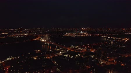 birdseye : 4K. Aerial pan of downtown Warsaw skyscrapers and bridge dark winter night light.