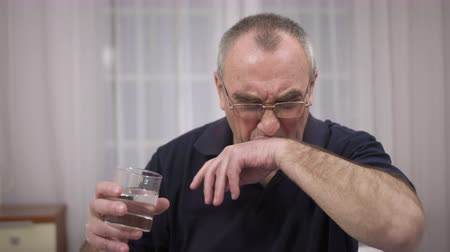nyel : elderly man drinks water, emotions of discontent and irritation Stock mozgókép