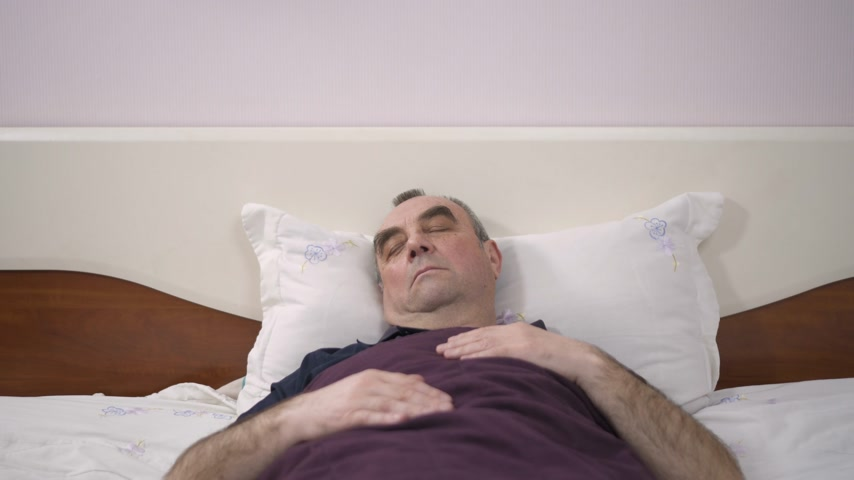 ébredés : An elderly man lies in his bed asleep, awakening from a dream, fear, anxiety