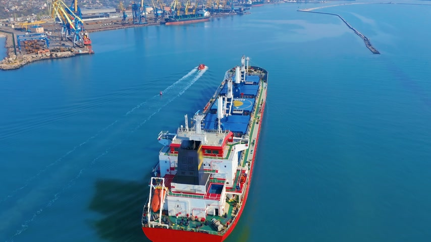 ithalat : Aerial view. Large cargo ship enters the port city with port cranes.