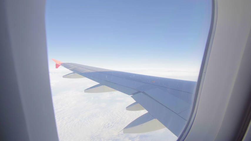 чирок : Airplane flight. Wing of an airplane flying above the clouds. View from the window of the plane. Aircraft. Traveling by air. 4K UHD video Стоковые видеозаписи