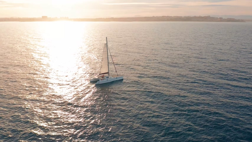 catamarano : Aerial view. Catamaran goes by sea, camera move closer and fly over vessel, on the sunset, Beautiful view Filmati Stock