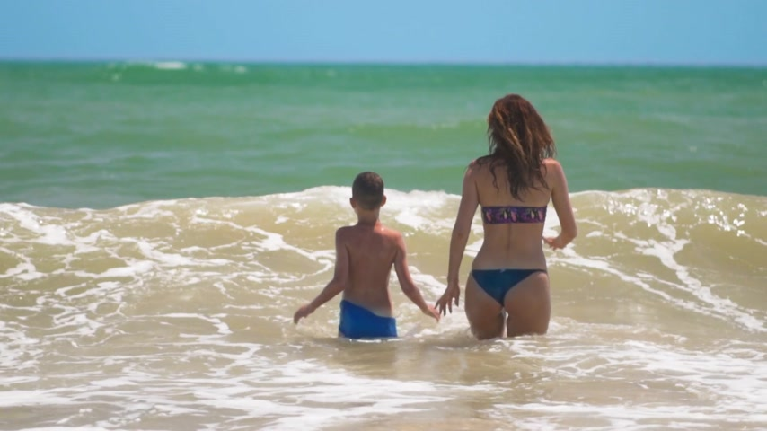 tyrkysový : The happy tanned kid happily swimming and jumping with mom in sea waves on summer sunny day at tropical beach.