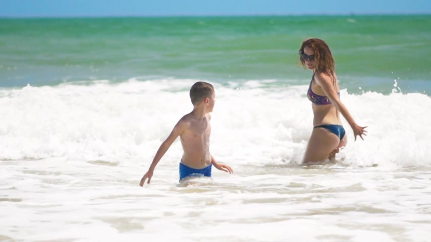 tyrkysový : mother and son jump into the sea on the waves, rejoise, have fun.