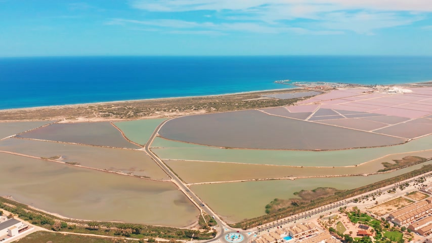 korumak : Multicolored salt lakes with coastal salt marshes, aerial view, video shooting with drone. Pink salt lakes and turquoise sea, aerial video.