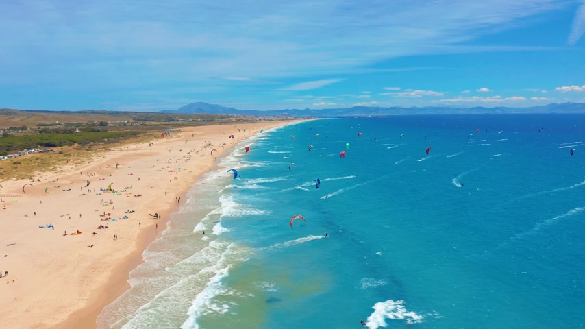 surfistas : Aerial view of kitesurfing extreme sport with the wind freestyle. Beautiful top view of nice beach. Lots of kites. Archivo de Video