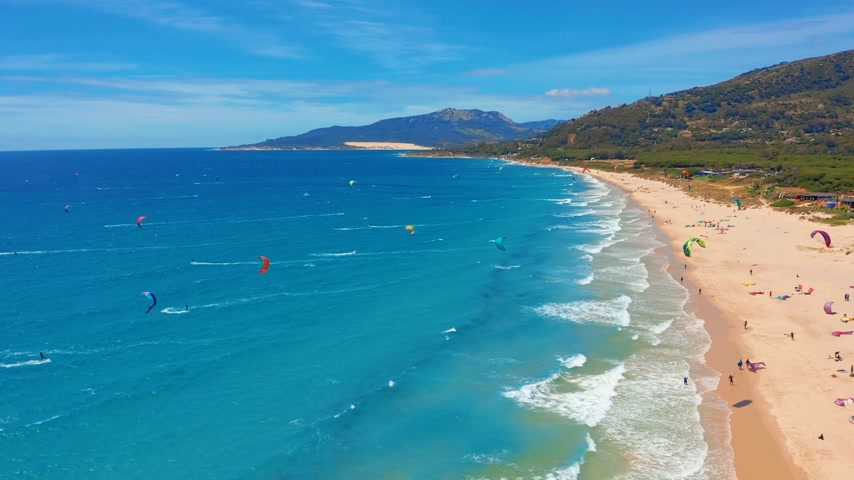 Андалусия : Aerial view. a large beach filled with kite surfers in tarifa, Spain. Стоковые видеозаписи