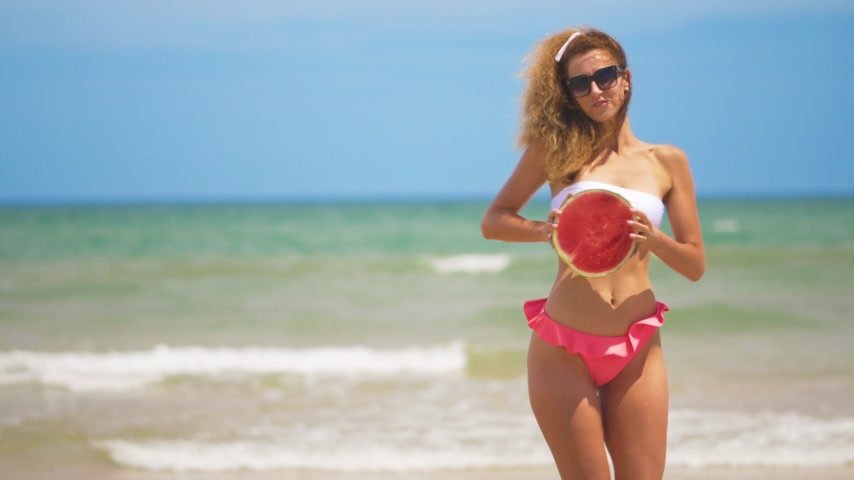 pastèque : Dancing girl with a half juicy watermelon on the background of a beautiful sea. Vidéos Libres De Droits