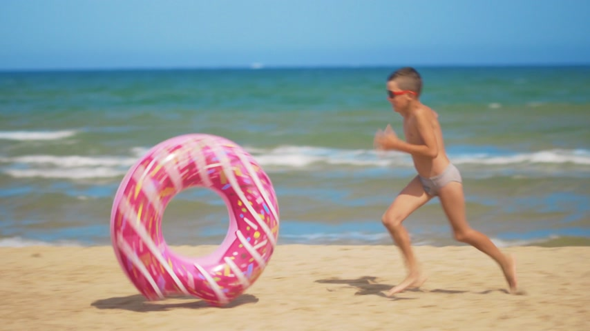executar : The boy runs along the beach with a pink inflatable donut, rolls it along the sand against the background of the sea. The concept of relaxation and fun. Stock Footage